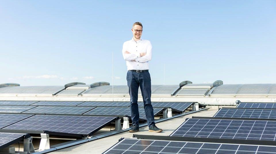 Mann steht auch einem Dach mit Solarpanels